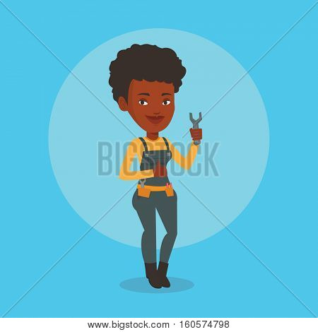 Young smiling repairman standing with a spanner in hand. An african-american repairman giving thumb up. Female repairman in overalls holding a spanner. Vector flat design illustration. Square layout.