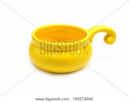 Single small clay empty yellow cocotte isolated on white front view horizontal closeup