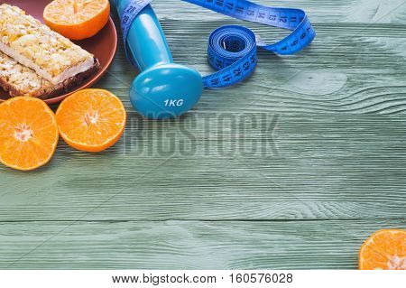 The concept of healthy lifestyle. Juicy citrus cereal bars dumbbell and measuring tape on green wooden table. Cereals and fruits - diet and breakfast