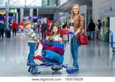 Young mother and two little kids, boy and girl, cute siblings twins at the airport. Funny children and woman, family traveling together, going on vacation via airplane and waiting with suitcases at terminal