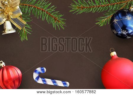 Christmas branches of spruce stick blue and red wavy dull balloon and decorative bell on dark background