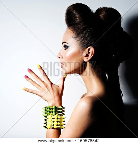Profile portrait of a Beautiful  woman wearing bracelet with thorns and mulricolored nails