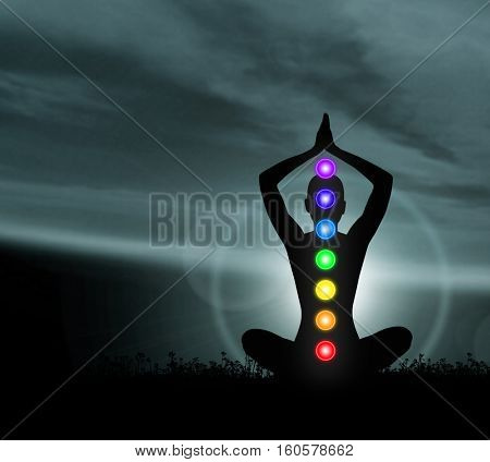 Trace of monk meditating in lotus position. Colored lights with chakra names over body. Yoga, zen, Buddhism, religion, recovery and wellbeing concept.