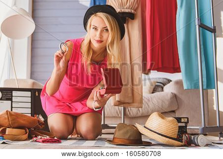 Confident young woman is maintaining fashion blog at home. She is showing bracelet to camera and smiling