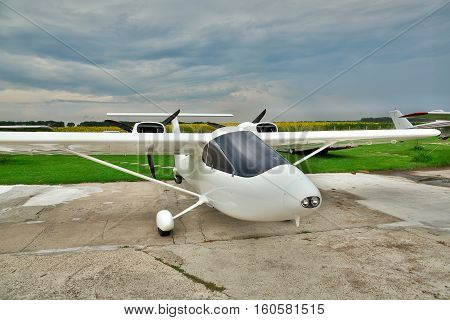Kiev Region Ukraine - July 19 2014: Light private twin-engine plane parked on an airfield with stormy sky and sunflower field on the background