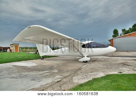 Kiev Region Ukraine - July 19 2014: Light private twin-engine plane parked on an airfield with stormy sky and hangar on the background