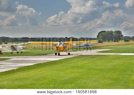 Kiev Region Ukraine - July 20 2014: Light private planes on the airfield on a sunny day with some clouds in the sky on the background