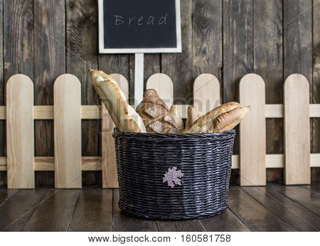 bread in a wicker basket on the wooden floor in the background of a wooden wall