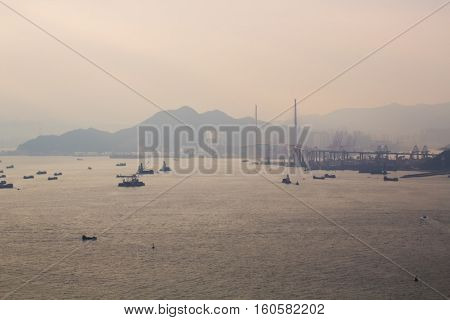 Many ships and boats in sea near cable-stayed in fog in Hong Kong, China, view from China Merchants Tower
