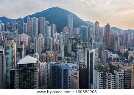 Residential buildings in sleeping area near green mountain in Hong Kong, China, view from China Merchants Tower
