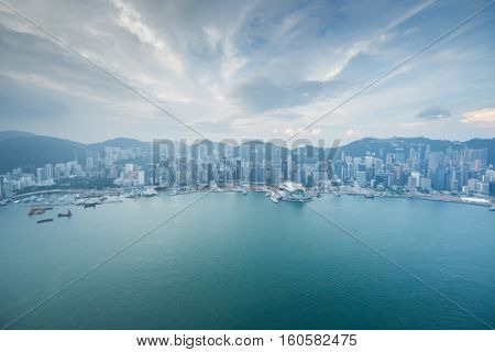 Shore and skyscrapers in fog on waterside and cloudy sky in Hong Kong, China, view from New World Center