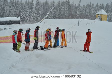 People on a mountain slope at ski resort. Ski instructor with skiers in ski school