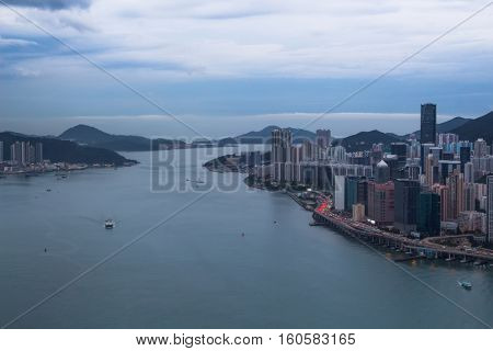Many skyscrapers on sea shore in business area, mountains at evening in Hong Kong, China, view from Harbourfront center
