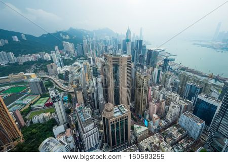 Skyscrapers, office buildings, coast in Hong Kong city, China at cloudy day, aerial view from Manulife Plaza