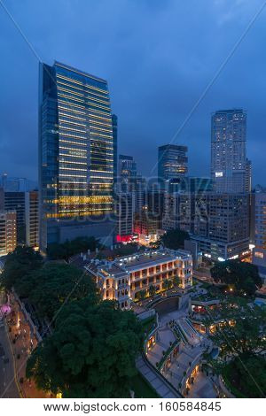 Skyscrapers and classical building with columns, stairs and galleries at evening in Hong Kong, China, view from Starhouse