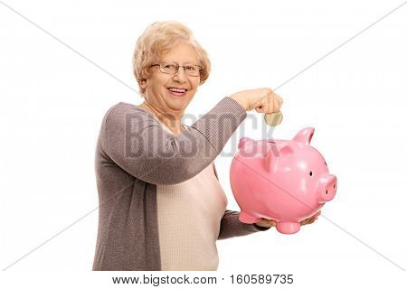 Happy elderly woman putting a coin into a piggybank isolated on white background
