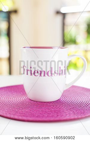 A cup with friendship quote on a pink placement on the white table in tne green garden. Natural light. Good mood.