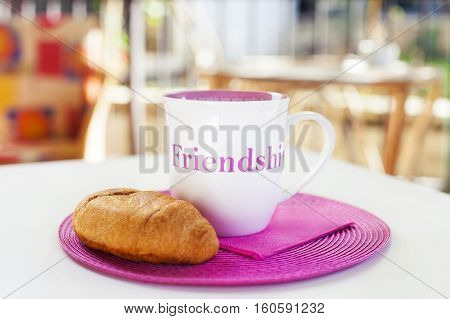 Cup of hot chocolate with tasty bun on a pink placement with a pink napkin. A friendship quote painted on the cup. Natural light. On white table in tne green garden.