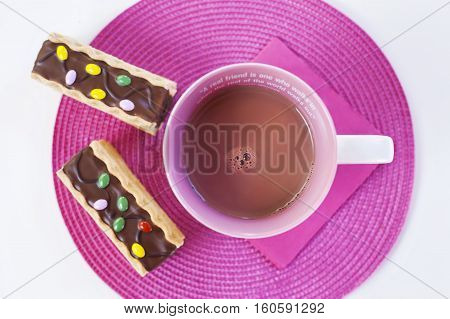 Cup of hot chocolate with funny chocolate cookies on a pink placement with a pink napkin. A friendship quote painted on the cup. Natural light. Isolated on white. Flat lay.