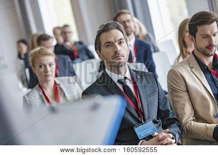 Businessman listening to presentation during seminar