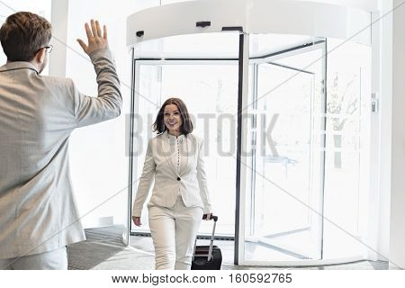 Happy businesswoman with luggage walking towards male colleague in convention center