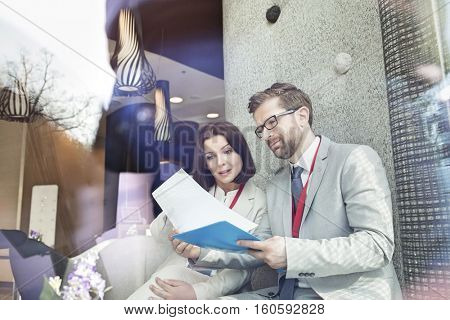 Business people reading document while sitting in convention center