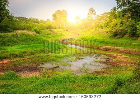 a dry river and green grass in countryside
