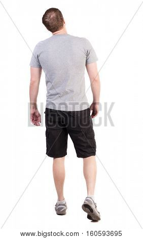 Back view of walking handsome man in shorts and sneakers.   Sports-dressed young man moves. backside view of person.  Isolated over white background. broad sporsmen in long black shorts are looking up