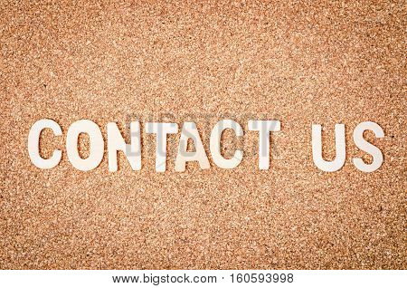 The Contact us word on wooden background.
