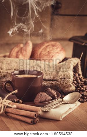 Cup fragrant hot coffee with bean chocolate sweet and croissant in vintage rustic style cinnamon steam smoke on wooden board for bracing morning breakfast