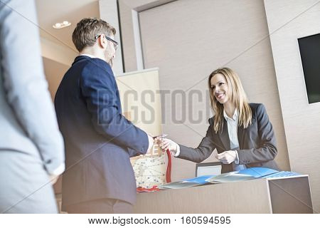Receptionist giving identity card to businessman at convention center