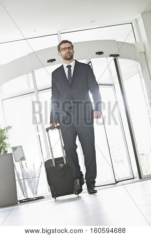 Confident businessman with luggage entering convention center