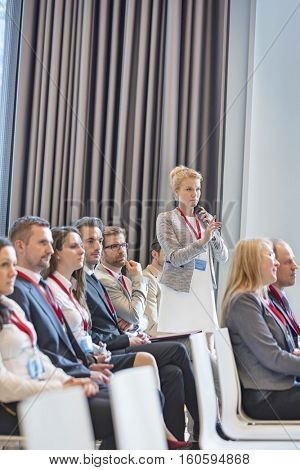 Businesswoman asking questions during seminar in convention center