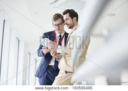 Businessmen using digital tablet in convention center