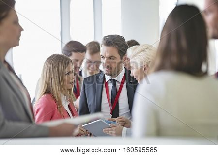 Business people discussing over digital tablet in convention center