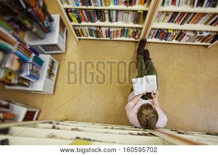 Reading in library aisle