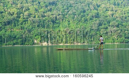 Ba Be, Bac Kan, Vietnam - Jun 10, 2010: Vietnamese local fisherman paddling a kayak made from the body of a big tree on Ba Be National Park, Bac Kan province, Vietnam
