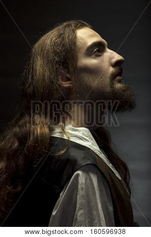 Personification of Jesus Christ man with long hair and beard peacefully looking up to the light