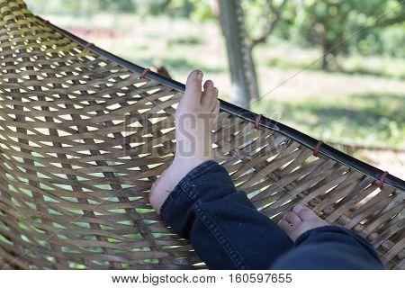 Feet Of Woman Resting, Relaxing, Sleeping On Rattan Cradle In Garden