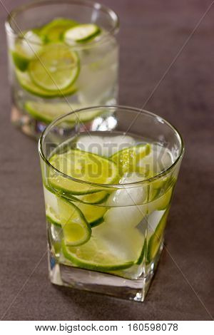 refreshing cocktail with green lemon and ice close up