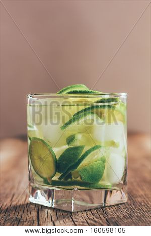 refreshing drink with green lemon and ice close up tinted photo
