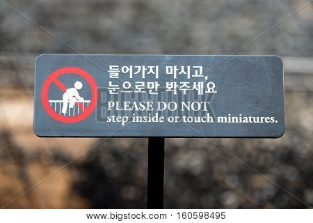A sign in a park - Please Do Not Step inside or touch miniatures. korean(Hangul)