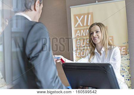 Happy receptionist giving identity card to businessman at convention center
