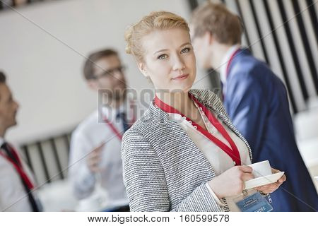 Portrait of confident businesswoman holding coffee cup at lobby in convention center