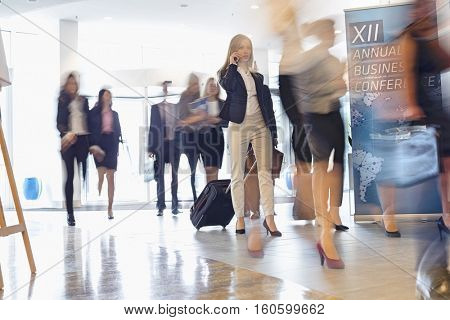Blurred motion of business people with luggage walking at convention center poster