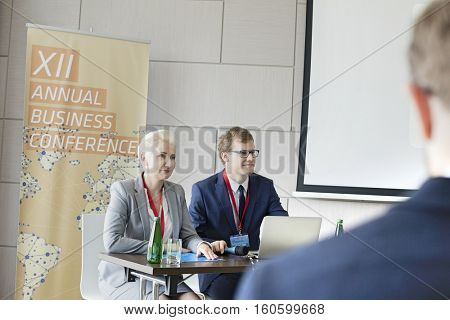 Business people sitting at desk in seminar hall