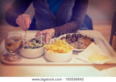 Woman in restaurant eating dinner salad with knife and fork