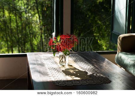 Ixora Flower On Wood Table And Brown Sofa Couch In Living Room Near Window