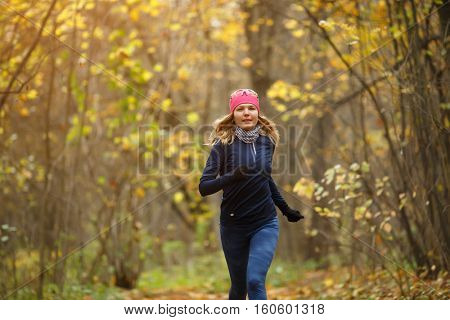 Woman running among autumn leaves