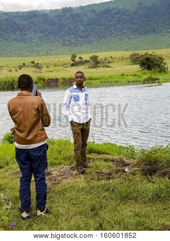 AFRICA, TANZANIA, MAY, 10, 2016 -Two men near Lake Manyara take pictures with a mobile phone in the Ngorongoro Crater Conservation Area, Tanzania.East Africa.